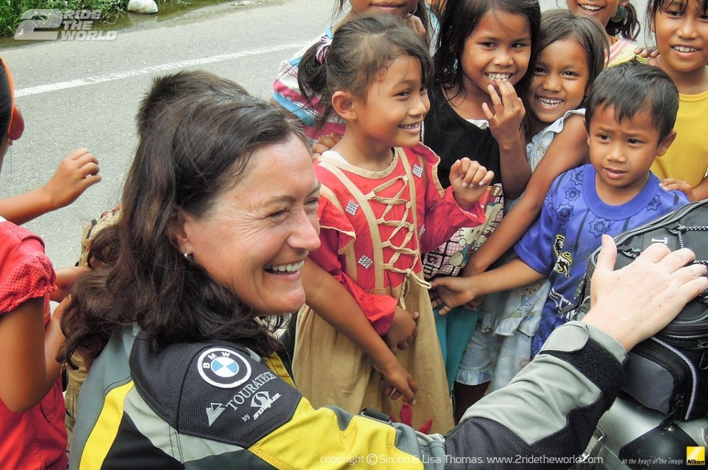 Women Who Ride: Lisa Thomas with a group of kids in Flores, Indonesia