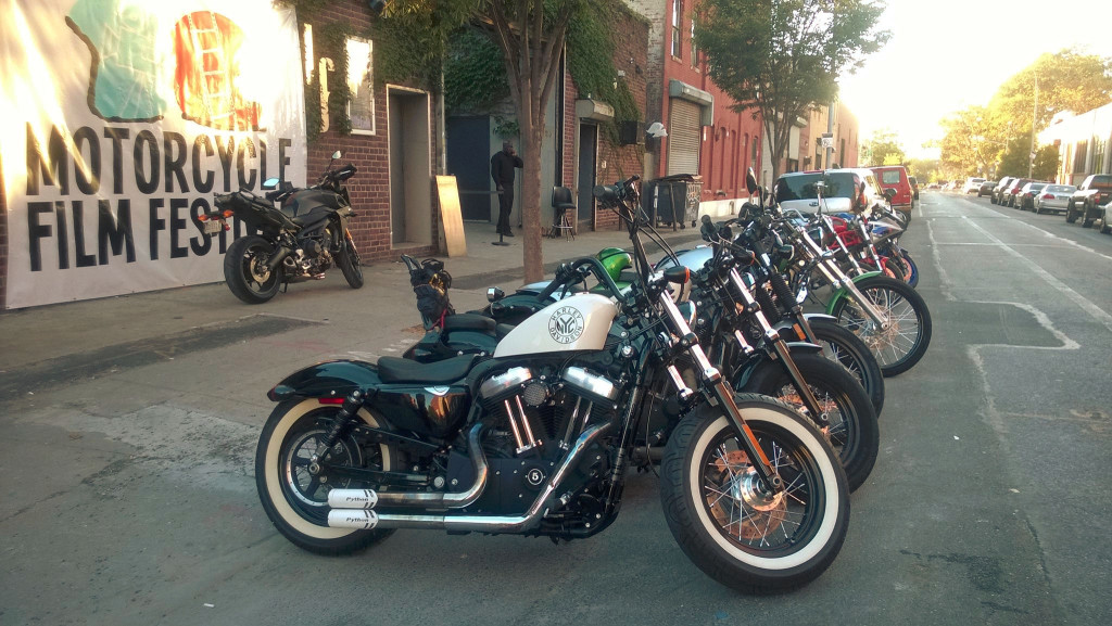 The 2015 Motorcycle Film Festival (Image depicts a row of motorcycles parked on the street in front of a building with a sign that says Motorcycle Film Festival)